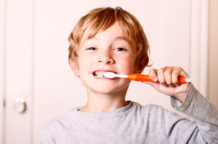 Boy brushing teeth with orange toothbrush