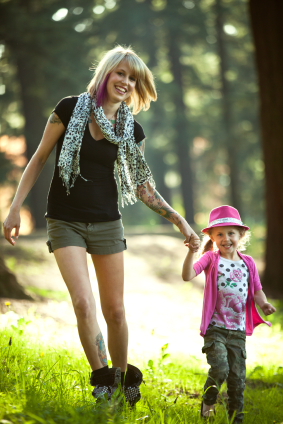 Mother with tattoo walking child in woods