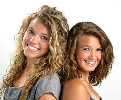 Two teenage girls one with braces smiling
