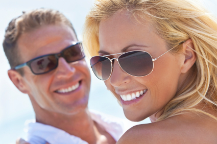 man and woman smiling with sunglasses on sunny day